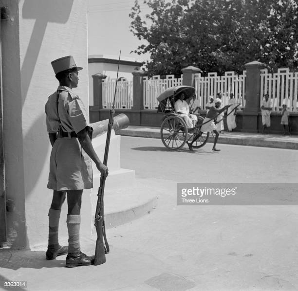 An Indian guard wearing a Frenchstyle kepi at the entrance to a government building in Pondicherry southeast India A rickshaw is passing in the...