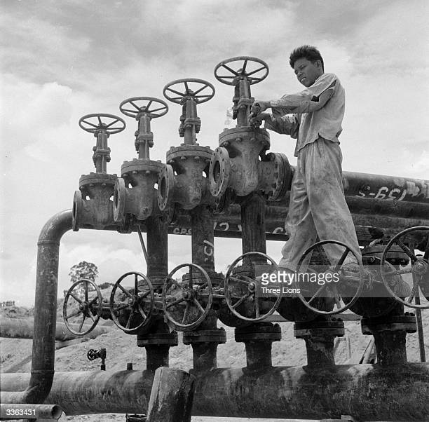 An oil worker operating the master valves which control pipe lines at an oil refinery on Sumatra Indonesia