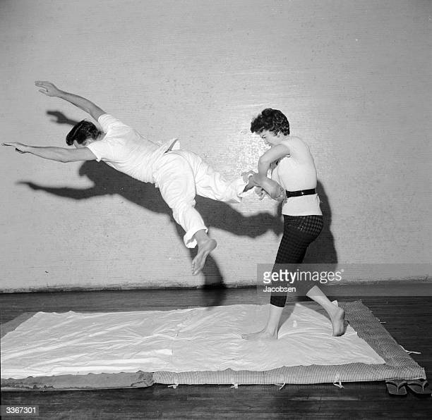 At a selfdefence demonstration a woman uses a judo heel and leg turnover against a kicking attacker As he kicks she grabs his leg and twists his...