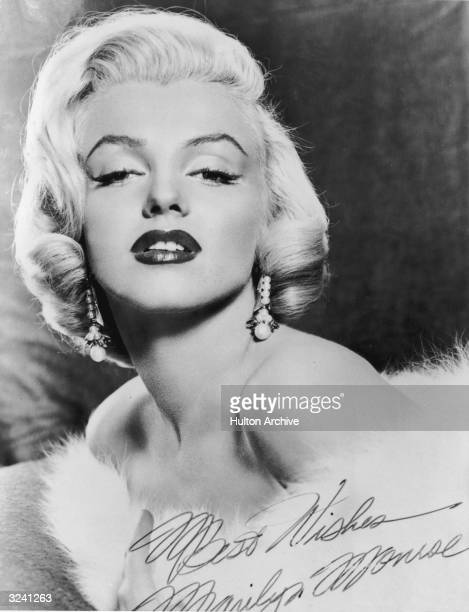 Autographed studio portrait of American actor Marilyn Monroe wearing a fur stole around her bare shoulders It reads 'Best Wishes Marilyn Monroe'
