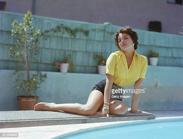 Circa 1955, British actor Joan Collins poses on a diving board over a swimming pool, 1950s.