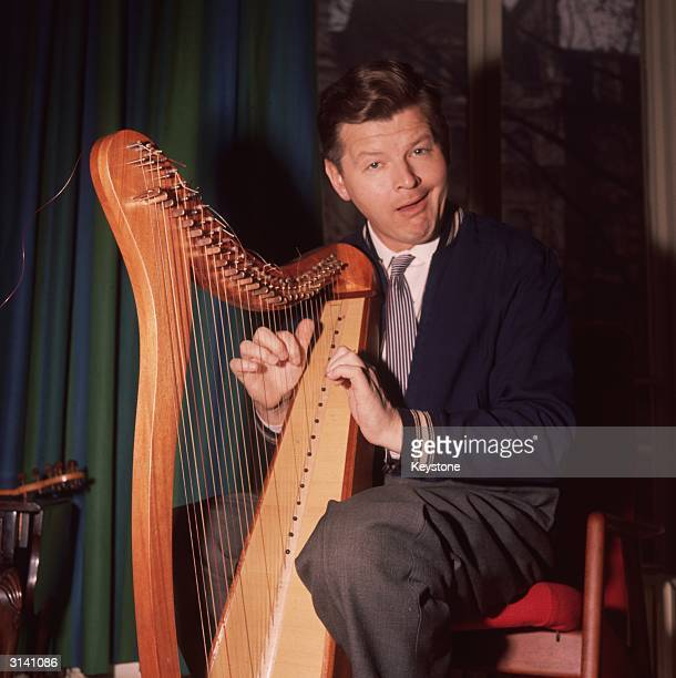 British comedian Benny Hill contrives to play the harp in a lascivious manner