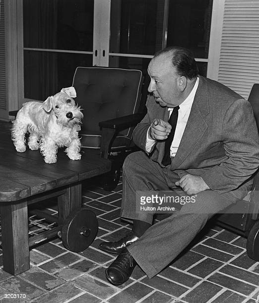 British film director Alfred Hitchcock points while coercing a terrier which is standing on top of a table on a patio deck to face the camera
