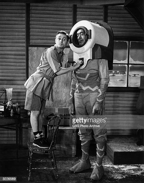 Britishborn actor and comedian Alan Young stands on a chair and makes a face while turning a knob on the helmet of 7' 7' actor Lock Martin who is...
