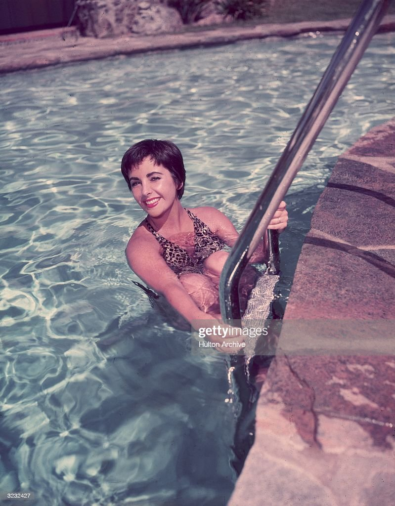 British-born actor Elizabeth Taylor, wearing a leopard-print swimsuit, holds onto a ladder in a swimming pool.