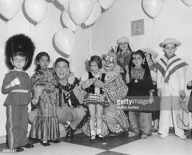 Buffalo Bob Smith and the clown Clarabell of the children's television series 'The Howdy Doody Show' kneeling among a group of children of various...