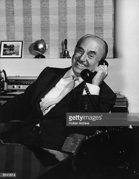 Canadianborn film producer Jack L Warner of Warner Brothers Pictures smiles while talking on a telephone 1950s