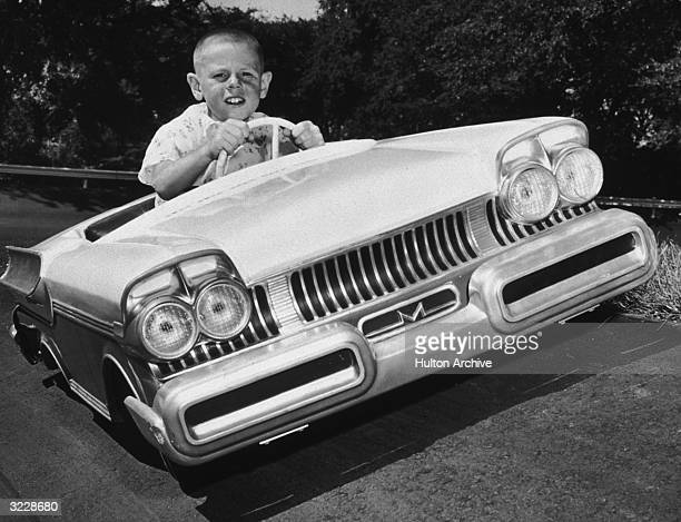 Canted image of eight yearold Billy Steinhauer driving a miniature Mercury convertible on the test track at the Ford Rotunda Showplace Dearborn...