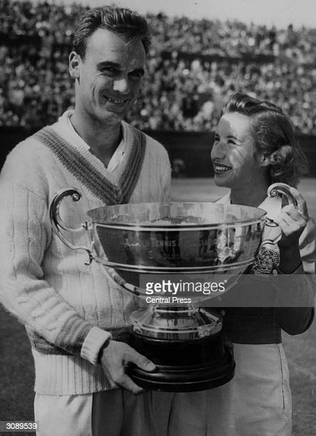 Captain of the US Davis Cup team Vic Seixas holds the trophy for winning the men's singles championship of Victoria assisted by Maureen Connolly who...