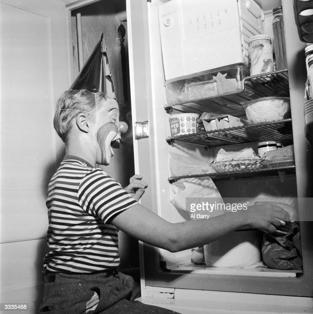 Child actor Ronnie Walken who later found fame as Hollywood star Christopher Walken raids the fridge at his home in Bayside Long Island