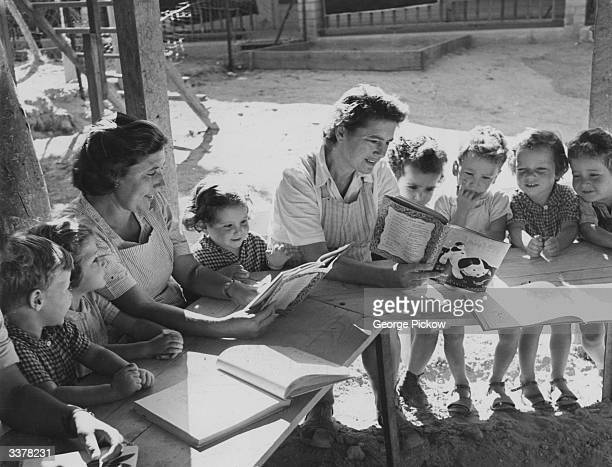 Children at a Kibbutz in Israel being cared for by trained guardians who are reading them a story