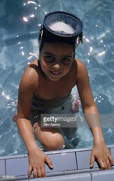 Christina Onassis the daughter of Greek shipping tycoon Aristotle Onassis climbing out of a swimming pool wearing a snorkel mask on her head