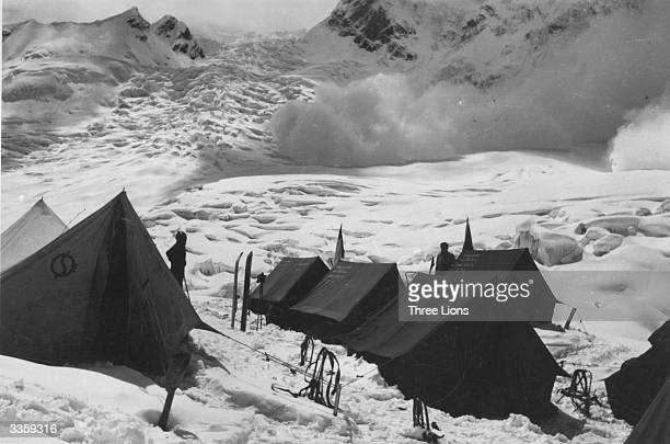 Climbers' tents pitched in the Himalayas with an avalanche occurring in the background