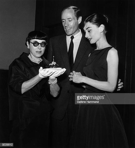 Costume designer Edith Head holds a cupcake with a lighted candle to celebrate her birthday as actors Mel Ferrer and Audrey Hepburn look on at a Don...