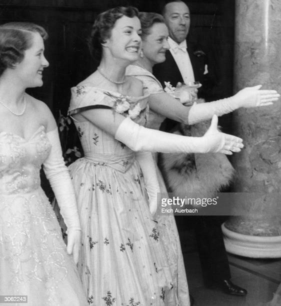 Debutantes greeting guests at a ball.