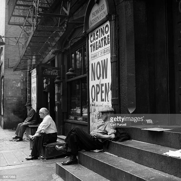 Elderly gentlemen rest on the steps outside the Old Howard Athenaeum in the Italian quarter of Boston Massachusetts