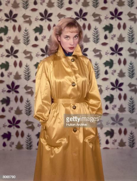 English actress Sylvia Syms wearing a gold raincoat