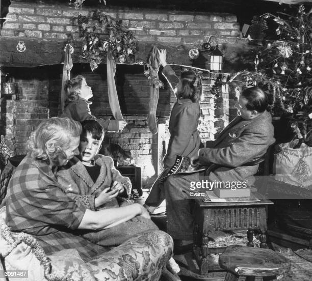 English children hanging their stockings above the fireplace on Christmas Eve in the hope that Father Christmas will fill them with presents overnight