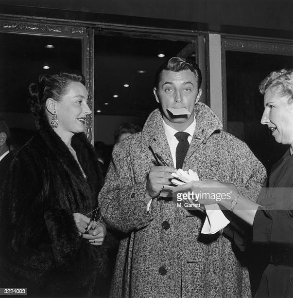EXCLUSIVE Actor Robert Mitchum stops to sign an autograph for a woman while exiting a nightcub with his wife Dorothy Hollywood California