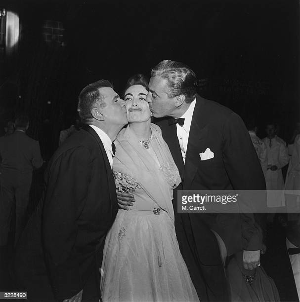 EXCLUSIVE Actors Ken Murray and Cesar Romero kiss actor Joan Crawford wearing a palecolored chiffon outfit from either side while she holds her chin...