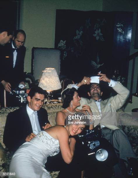 Actors Linda Christian and Tyrone Power look at snapshots with Rocky Cooper at a party at Gary Cooper's house.