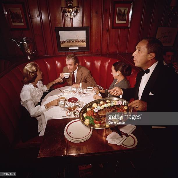 EXCLUSIVE American actor James Stewart his wife Gloria and an unidentified woman have coffee while sitting in a booth at Chasen's restaurant Los...