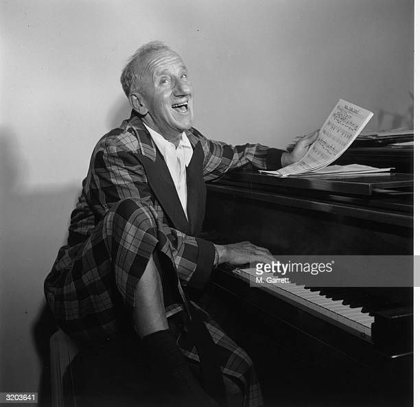 American actor Jimmy Durante wearing a plaid robe at home, seated at a grand piano with one knee elevated, singing and holding sheet music, Los...