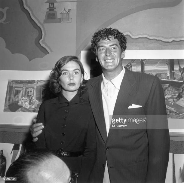 EXCLUSIVE American actor Victor Mature grins as he stands with his arm around Britishborn actor Jean Simmons inside a nightclub with paintings behind...