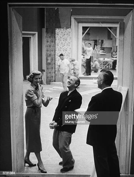 EXCLUSIVE American actress Lauren Bacall and British actor David Niven laugh while standing in a doorway during a rehearsal break on a set possibly...