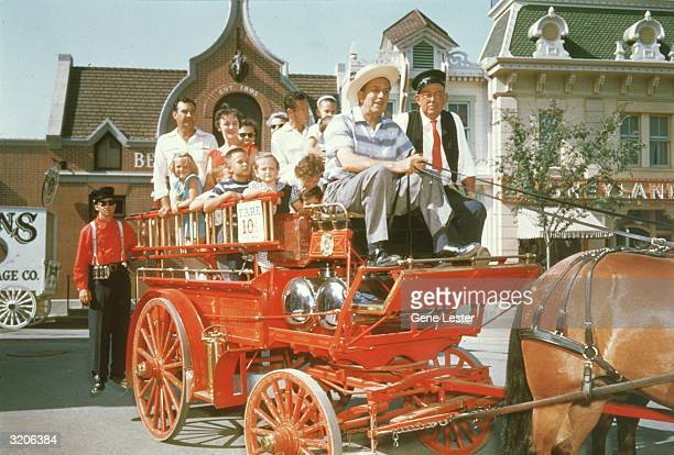 American animator and film studio founder Walt Disney sits in the front of a red, horsedrawn fire wagon, holding the reins, Disneyland, Anaheim,...