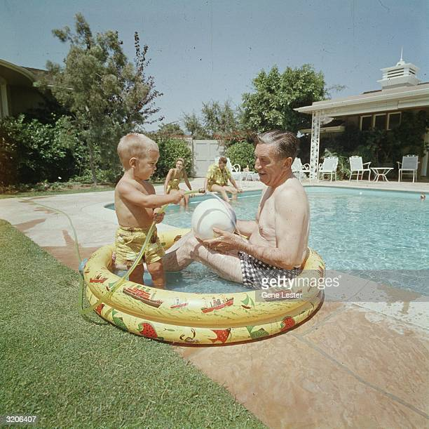 EXCLUSIVE American animator and film studio founder Walt Disney sits and plays with his grandson in a child's inflatable pool next to a larger...