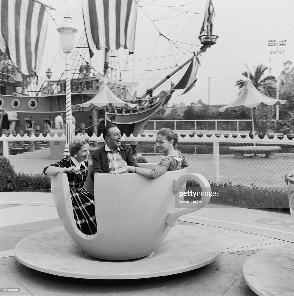 American animator and producer Walt Disney (1901 - 1966) and his wife, Lillian, and their daughter, Diane, ride a spinning tea cup at Disneyland, shortly after its opening, Anaheim, California.