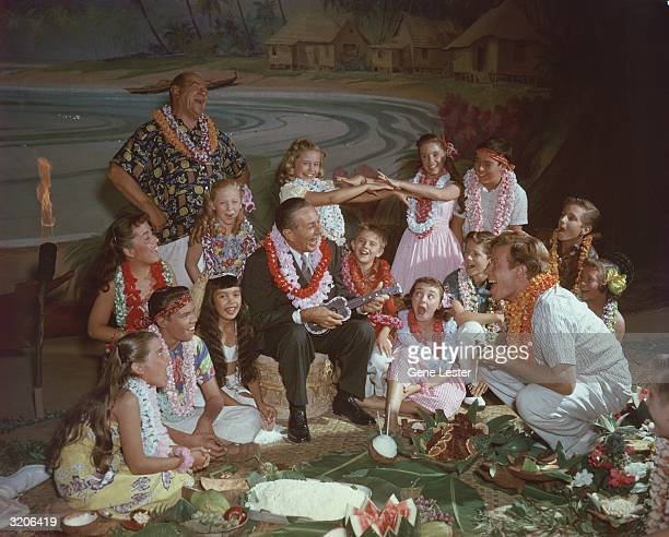 EXCLUSIVE American cartoonist and film producer Walt Disney sings and plays a ukulele for a group of children during a luaustyle picnic in front of a...