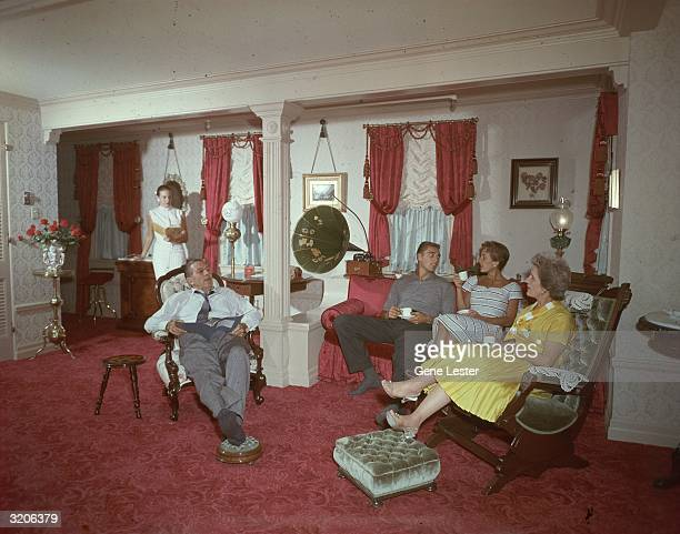 EXCLUSIVE American cartoonist and film producer Walt Disney sits with his family while they read and drink tea or coffee in a turnofthecentury...