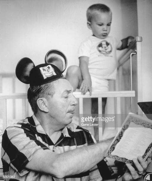 American cartoonist and movie studio head, Walt Disney , wearing Mickey Mouse ears, reads his grandson a story from a children's book. His grandson...