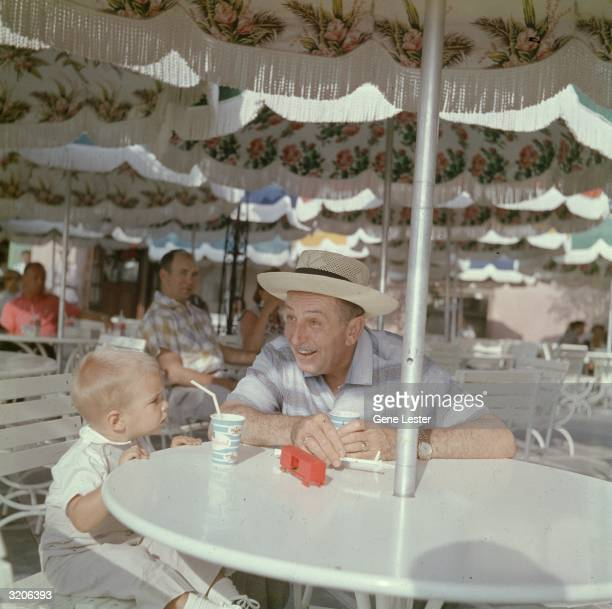 EXCLUSIVE American cartoonist Walt Disney sits with his grandson at an outdoor patio table while visiting Disneyland in Anaheim California Both drink...