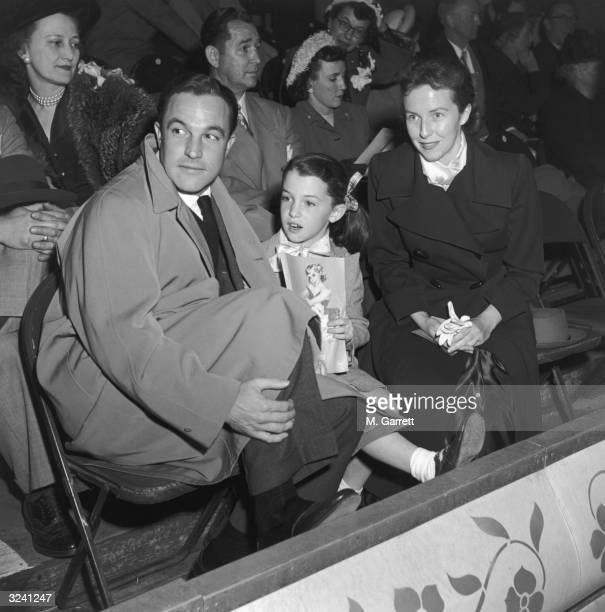 EXCLUSIVE American dancer and actor Gene Kelly his wife Betsy Blair and their daughter Kerry holding a program sit in the stands at an Ice Follies...
