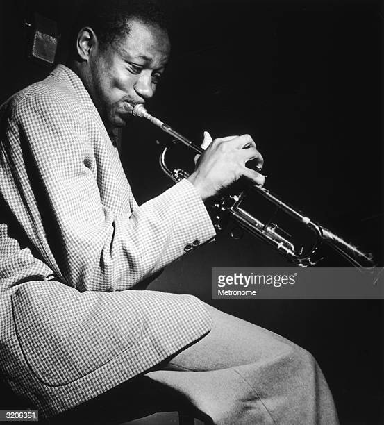 EXCLUSIVE American jazz musician Clifford Brown wearing a houndstooth jacket and flannel pants playing a trumpet in a recording studio