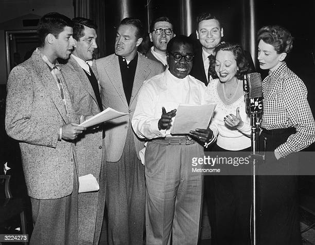 EXCLUSIVE American jazz trumpeter and bandleader Louis Armstrong stands with a script at a radio microphone joined by entertainers Jerry Lewis Dean...