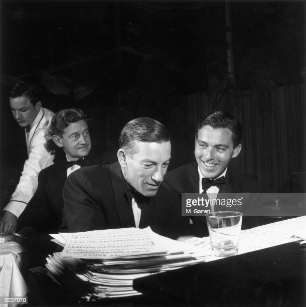 EXCLUSIVE American songwriter Hoagy Carmichael and Fred Korger sitting at a piano during a Hollywood party Hollywood California On the piano is a...