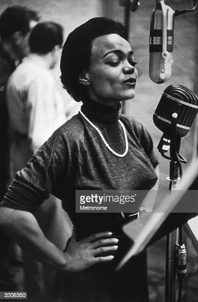 EXCLUSIVE American vocalist and actor Eartha Kitt stands with her hands on her hips while singing into a microphone in a recording studio She is...