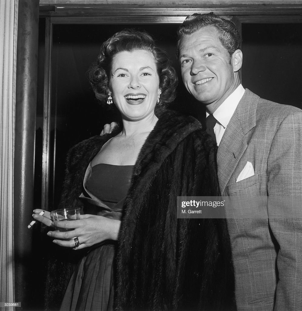 Barbara Hale, smoking a cigarette while holding a drink, poses with Bill Williams (1916 - 1992) in a nightclub, Hollywood, California. Hale is wearing a fur coat.