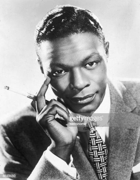 EXCLUSIVE Headshot portrait of jazz singer and pianist Nat King Cole holding a cigarette and looking at the camera
