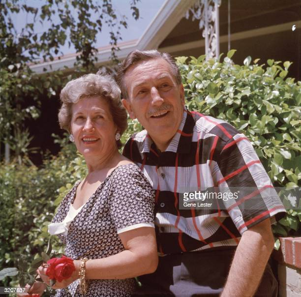 EXCLUSIVE Portrait of American animator Walt Disney and his wife Lillian smiling while posing outdoors in front of shrubs at their home Lillian holds...