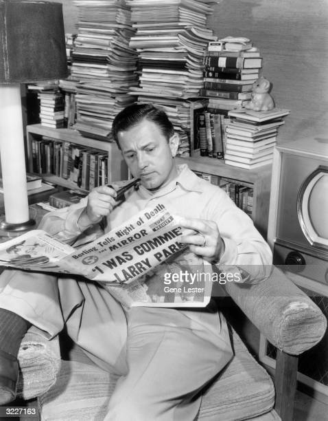 Portrait of American director Edward Dmytryk smoking a pipe while reading 'The Mirror' in a living room, 1950s. The newspaper's headline reads, ''I...