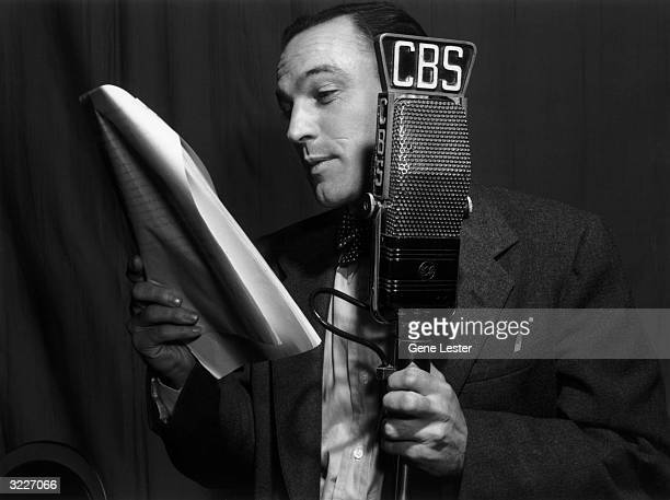 EXCLUSIVE Profile headshot of American actor and dancer Gene Kelly reading from a script during a CBS radio play broadcast of the show 'Hollywood...