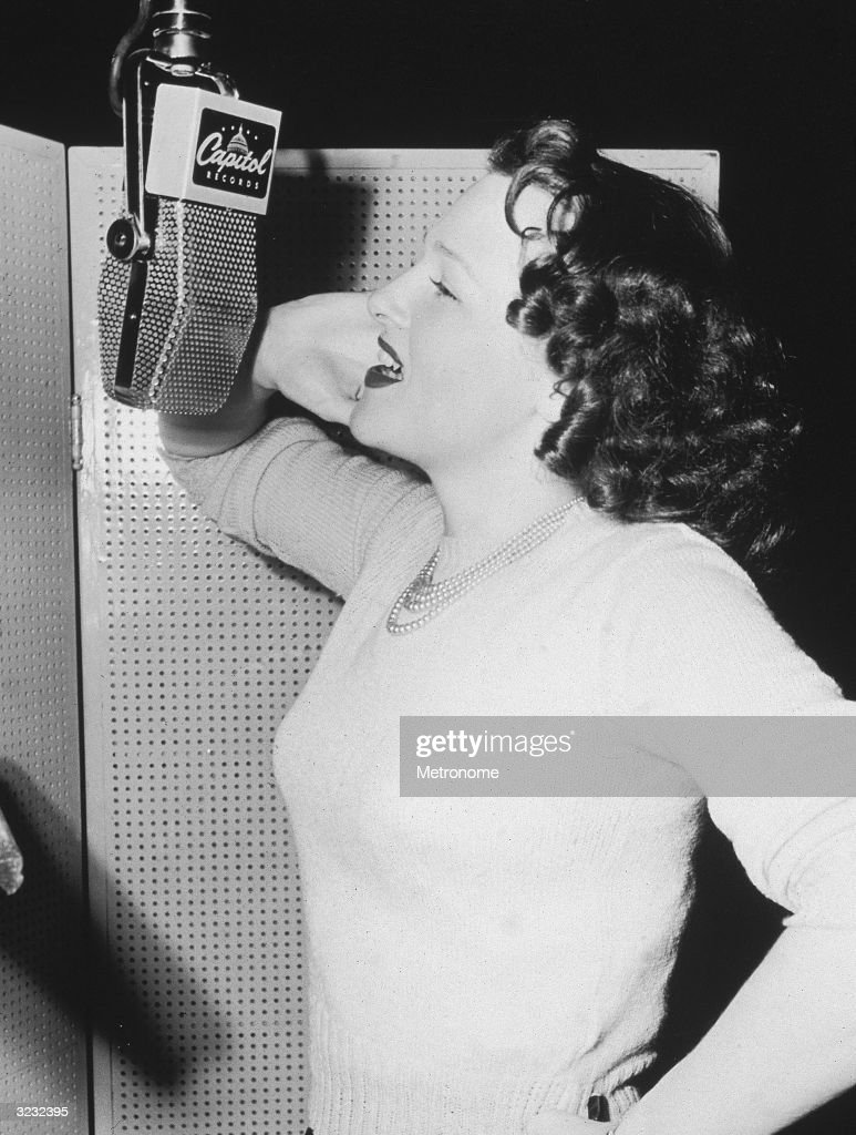 Profile view of American pop and jazz singer Jo Stafford singing at a microphone in a recording studio. There is a hinged acoustic wall around her. She wears a light-colored sweater and a pearl necklace.