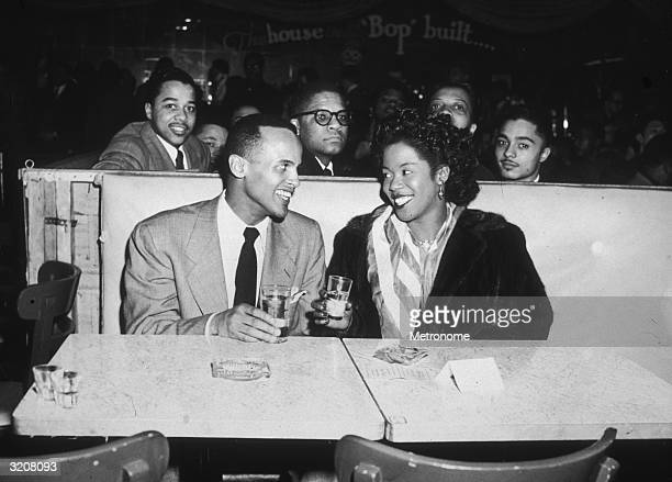 EXCLUSIVE Singer and actor Harry Belafonte Jr sits at a nightclub dinner table with jazz singer Sarah Vaughan preparing to toast with their drinking...