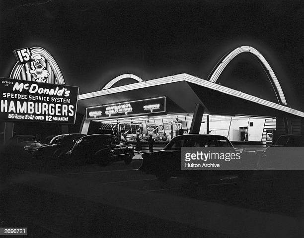 Exterior view of the first McDonald's fast food restaurant with its neon arches illuminated at night, Des Plaines, Illinois.