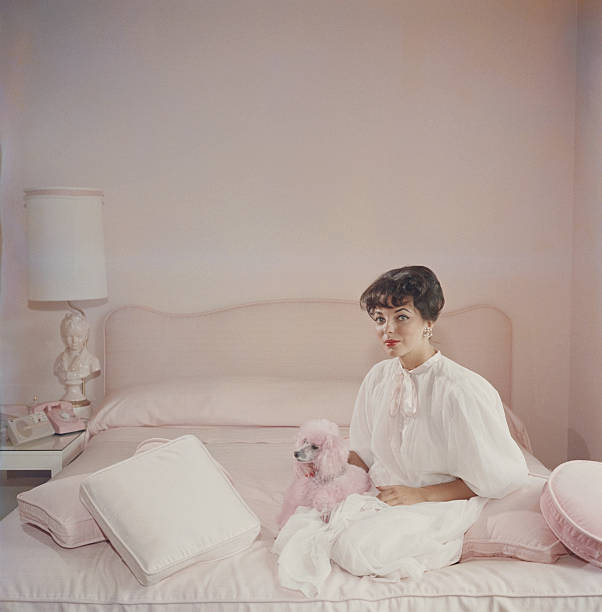 Film star Joan Collins in a pink and white bedroom...